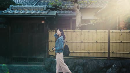 sırt çantasıyla : elegant lady walking on the street next to the Japanese style house and flicks her long black hair Stok Video