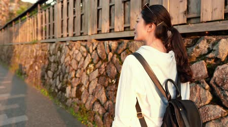 bamboo curtain : pretty female backpacker walking fast on Japanese street, going back to hostel Stock Footage