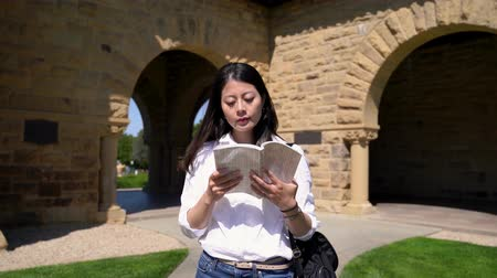 Франциско : the fast motion of a female exchange student reading a book while walking on campus in a big sunny and windy day.