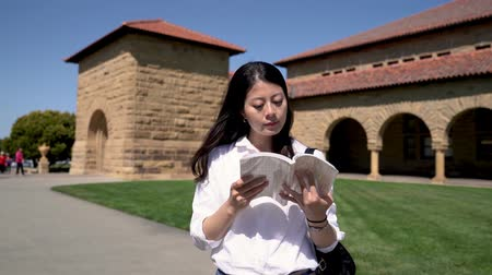 Франциско : young international student reading a book while walking in the square on campus after a full schedule of classes.