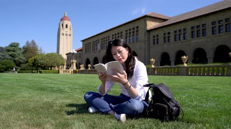 campus universitario : a diligent international student reading a book and sitting on the grass for a break during a full day of classes.