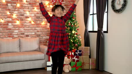 deer : cute christmas girl in red dress cheerful jumping with her new gift. dancing in the cozy living room with a decorated christmas tree in the background. xmas celebration concept.