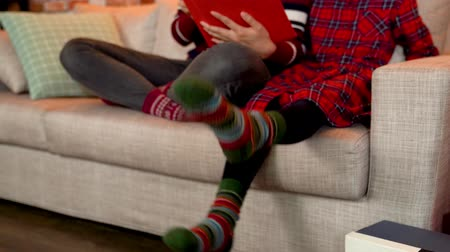 happy socks : family xmas holiday concept. parent and kid relaxing on the couch reading christmas fairy tales story. little child moving feet up and down. Stock Footage