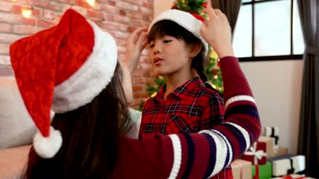 ukłon : mom helping cute little girl wearing santa hat and flicks her hair. lovely child telling story to her young mother at home on xmas eve. merry xmas and happy new year are coming Wideo