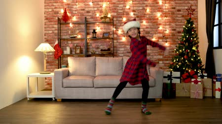 ano novo chinês : cute little girl joyfully dancing in the living room alone. girl kid with santa hat happy jumping in the living room on christmas eve. cozy room with colorful decorated chrismas tree. Vídeos