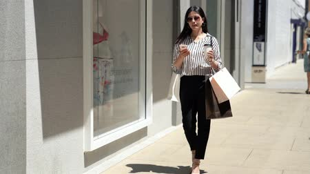 nakupování : full length of office lady walking on the street texting or reading news on smart phone using app. asian lady shopping in outdoor stanford mall on sunlight day. businesswoman ini holiday lifestyle. Dostupné videozáznamy