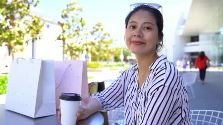 tea bag : young Asian woman smiling to camera with colorful shopping bags on the table. girl with sunglasses having afternoon tea outdoor and relaxing enjoy life. beautiful lady in sunny weather holiday.