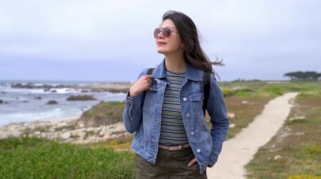 miglio : young traveler seeing in the ocean view in the trip in california state route 1. confident woman travel Japan summer holiday girl enjoying sea. backpacker with sunglasses walking on the path. Filmati Stock