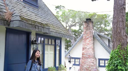 miglio : asian girl walking through the green garden out from home living in carmel by the sea. young lady with camera travel in the morning. beautiful woman surrounding by the vintage building in us.