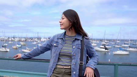 halászok : asian female backpacker visiting fishermans wharf first sightseeing spot from hotels in the morning in spring vacation. young lady joyful relaxing by the bay with many boats on the ocean. Stock mozgókép