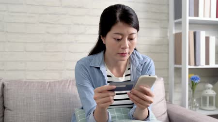 подтверждать : asian woman shopping on online shoes store with credit card on big bargain sale. Pretty lady buying clothes with special price on internet shop. young girl using cellphone on sofa. Стоковые видеозаписи