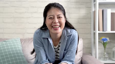 family watching tv : Cheerful woman sitting at home on the comfortable couch in the bright cozy living room. attractive asian joyfully laughing while relaxing watching funny movie on tv. young girl relaxing at home.