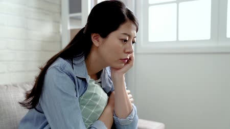 sentido : slow motion of an upset asian mom thinking how to teach her annoying children. young mother confused and putting her hand on the chin. attractive woman unhappy sitting at home in the sunlight living room.