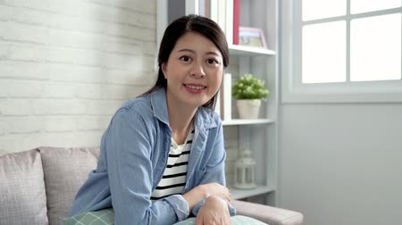 minder : elegant businesswoman smiling face to camera sitting in the bright living room with white wall. young office lady relaxing at home after work. mom joyful waiting for family to come home.
