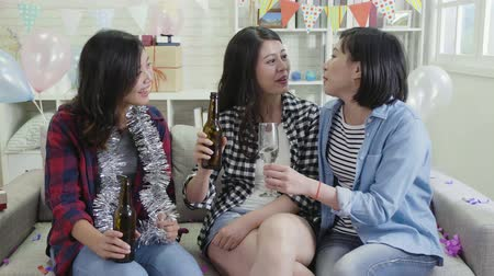 楽しんで : group of friends happy chatting drinking alcohols in house birthday party. young ladies holding beers and champagne surrounding colorful gift boxes and balloons. decorted living room at bright home.