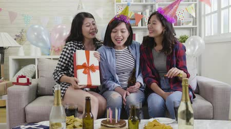 champagne bottles : slow motion of happy sisters celebrating birthday together at home in living room giving gift boxes and cheerfully talking. young girlfriends hugging on couch in house party indoor colorful balloons. Stock Footage