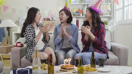 hediye kutusu : young ladies happily singing songs celebrating birthday at home. house party with burning candles on cake surrounding champagne. joyful attractive asian women clapping hands on sofa indoor.