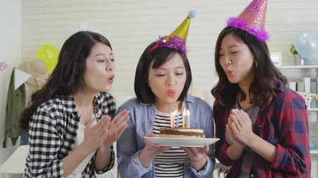 sisters : young female asian with colorful hats celebrating birthday party at house indoor. beautiful girls clapping hands holding cake and blowing candles together. cheerful ladies laughing during home life. Stock Footage