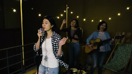 cantora : slow motion of young singer holding microphone singing in outdoor karaoke party at night. beautiful ladies dancing with beer and playing guitar in background. dark rooftop party friendship concept.