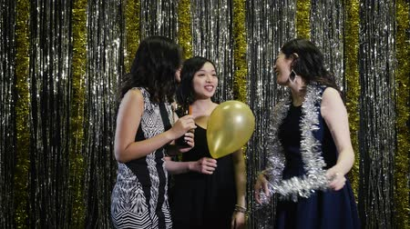 friendship dance : slow motion asian women at nightclub dancing chatting cheerfully. beautiful girls partying female models at club night out with gold and silver metallic on background. Clubbing concept for nightlife.