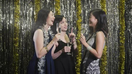 chill out : slow motion clubbing girls cheers wine and chatting cheerfully. Sexy Asian female models night lifestyle at club. group of fashion women holding glasses of champagne touching together. Stock Footage