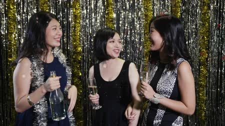 cheers : slow motion young female asian love alcohol holding bottled of champagne chatting at nightclub. beautiful ladies in sexy party dress with surprised shocked face at club. Clubbing concept nightlife Stock Footage