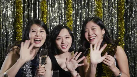 call out : quick motion of young party ladies love night out with best friends with drinks at single party. cheerful asian women waving hands to camera on video phone call. silver gold metallic background.