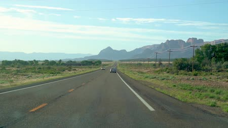 ARIZONA, USA - MAY 31, 2018: highway tour trip in america car driving on the road in countryside along the green meadow with blue sunny sky. beautiful nature desert mountain scenery in background.