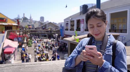 обмен сообщениями : Cheerful woman face to camera smiling attractive. young girl backpacker using cellphone searching hotel near pier 39 outdoor on second floor. busy weekend market with people shopping on summer sale.