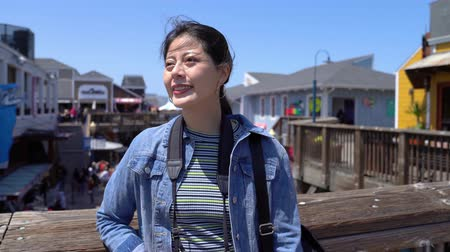 bezoeker : Happy backpacker photographer standing on second floor outdoor and smiling enjoying the wind blowing. popular holiday destination for people shopping on summer sale on sunny day. travel usa lifestyle Stockvideo
