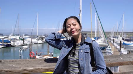 boat tour : young lady tourist travel in san francisco usa visiting famous tour attraction fisherman wharf. girl traveler relying on wooden handrail on suuny day relaxing enjoy the view. fishing boats on pier 39 Stock Footage