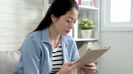 see off : happy asian office lady wearing casual suit relaxing sitting on couch in the morning reading newspaper. Joyful businesswoman resting at home on weeked lifestyle concept. bright white sunshine room. Stock Footage