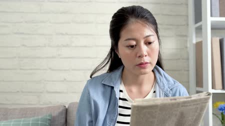 see off : happy young lady agree with the article nodding head. close up video asian housewife sitting on couch reading newspaper in bright house. wife at home in daytime lifestyle concept.