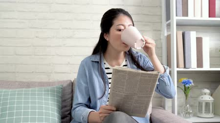 clean room : happy young woman engrossed newspaper while sitting in cozy living room at home with sunlight from window. beautiful housewife relaxing reading article drinking cup of tea on couch in house.