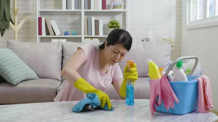 домохозяйка : slow motion of young housewife trying hard to remove the dust on marble table in living room. housekeeper wearing yellow protective gloves using rag wiping cleaning sitting on floor concept.