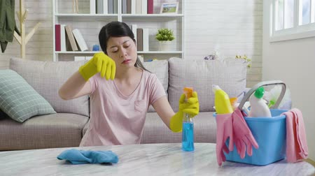 хмурый : tired wife doing housekeeping wants to rest. unhappy lady frowning and stopped her housework feeling enough. young mom cleaning wiping marble table with sprayer and rag. Стоковые видеозаписи