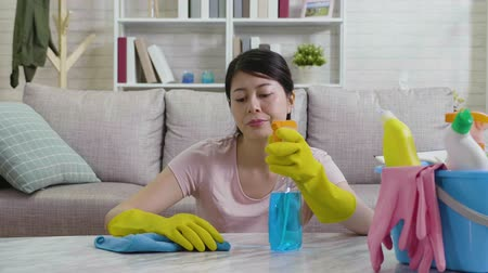 wipe away : Young housewife in gloves doing housekeeping sitting down with an unhappy face. housekeeper feeling tired wiping away sweats and dissatisfied with her housework while cleaning the table with rag. Stock Footage