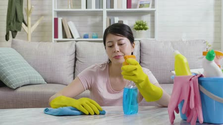 sprayer : slow motion of young housewife dissatisfied with cleaning house sitting down on floor resting a while wiping sweats. tired female housekeeper lifestyle concept. unhappy asian wife doing housework.