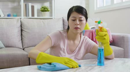 temizleme maddesi : tired mom doing housekeeping with an unhappy face. young housewife wiping table with rag wearing protective gloves and holding sprayer. full of cleaning product in bucket on comfortable sofa. Stok Video