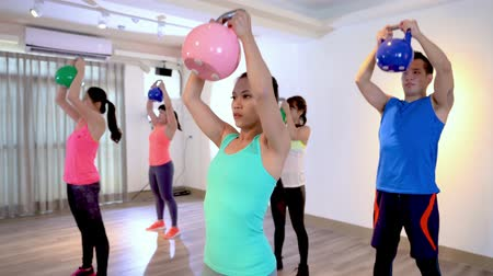 репетитор : Attractive sporty people holding kettlebells high to the roof in a fitness group with one hand raising up indoor at health club. young asians wearing sport shirt love workout at gym lifestyle concept
