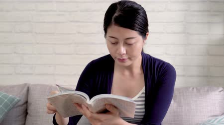 kniha : asian housewife keep turning page reading the travel tour book in the living room. elegant smart lady sitting on couch wearing comfortable casual suit at home in daytime. girl spending leisure time.