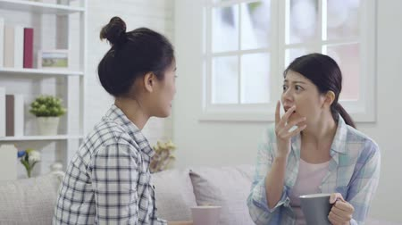 sisters : slow motion of amazed young asian woman with open mouth hand covering sitting on a couch in the living room in a house interior. beautiful female roommates talking seriously and frowning.