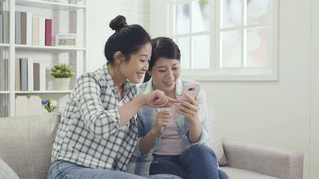 alku : slow motion of young asian girls sharing cellphone looking at the site together choosing party dresses online bargain price on summer sale. excited friends cheerfully pointing finger to screen mobile Stock mozgókép