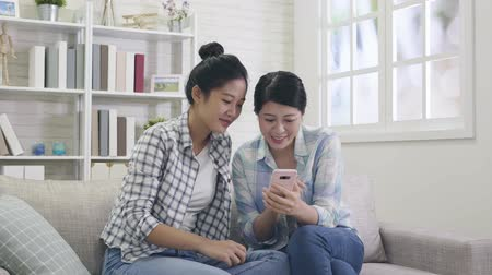 barganha : slow motion of sisters using smartphone touching screen watching funny video laughing cheerfully. young ladies shopping on christmas sale online store by mobile at home sitting on comfortable sofa.