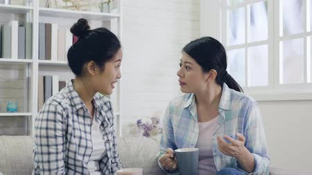 wistful : slow motion angry fresh woman complaining about her boss. young asian girls frowning talking about the unbelievable things and feeling shocked surprised. two casual ladies on couch chatting with tea.