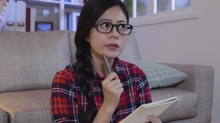 espetáculos : slow action smart female college student in glasses studying hard late hours in the night at home. young girl holding pen thinking daydreaming for new idea of presentation in final exam of semester. Stock Footage