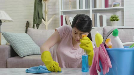 хмурый : slow motion of young housewife wiping table using cloth and detergent cleaner. beautiful asian woman doing housework hard in daytime along at home prepare for new year. housekeeping concept.