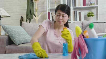 хмурый : fast motion young housewife trying hard remove dust on table spraying detergent wiping. beautiful woman in yellow protective gloves using clothing tidy up room. cleaning supplies in bucket