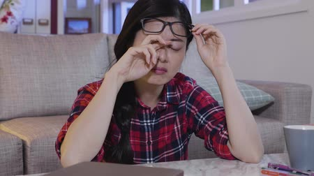 dörzsölés : Tired female student is rubbing her eyes after long reading at middle of the night. young college girl wearing glasses feel painful sleepy frowning. woman keep writing doing homework stay up late. Stock mozgókép