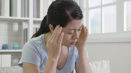 dor de cabeça : slow motion of tired housewife with headache at home. young asian woman feeling sick shaking head sitting in sofa in living room. girl touching her temples feeling stress.